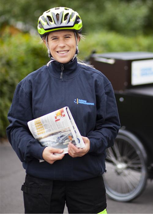Postdistributör leendes bredvid sin postcykel med tidning i handen