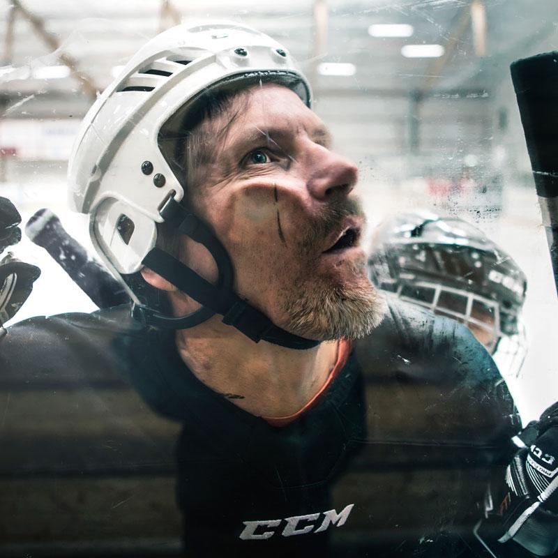 Hockeyspelare trycks upp mot plexiglaset i ishockeyarena